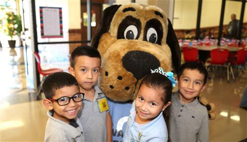 4 elementary students with Biscuit, a dog mascot